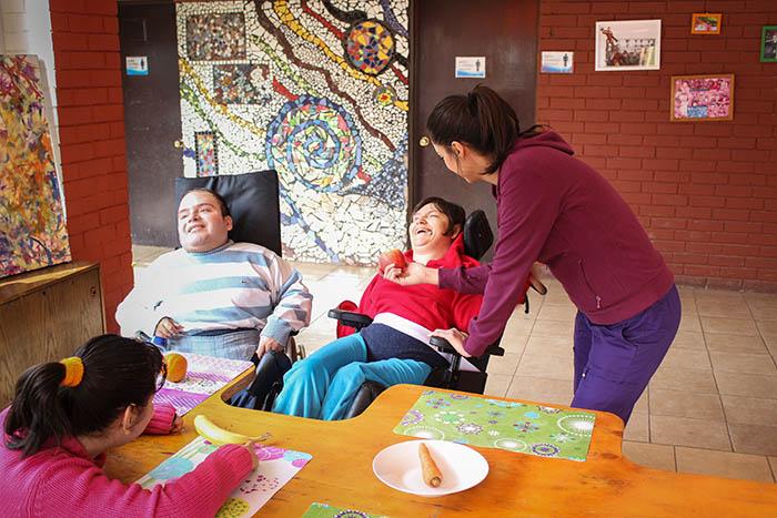 En la foto se ve dos jóvenes en la hora de la colación que ríen mientras comparten con las demás personas