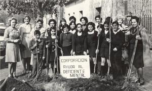 En al foto se ve un grupo de niños de la Fundación con monitoras en blanco y negro que están en un jardín
