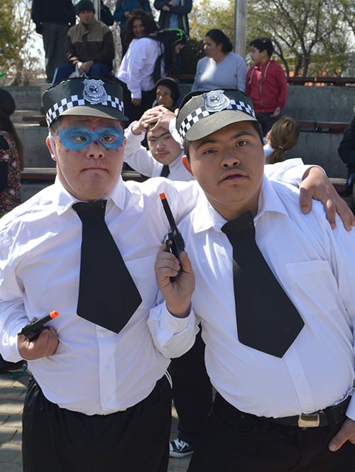 En la foto, dos niños de la fundación se abrazan mientras juegan a los policias, posando para la cámara