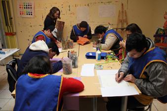 En la foto se ve un grupo de jóvenes de la fundación Coanil que trabaja en un taller artístico sobre un mesón