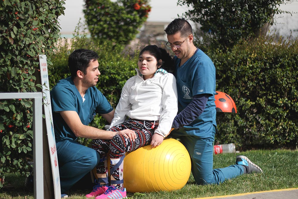 En la foto dos profesionales trabajan con una niña de la fundación ayudando a mejorar su movilidad