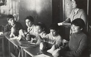 En al foto se ve un grupo de niños de la Fundación con monitoras en blanco y negro realizando trabajos en una sala